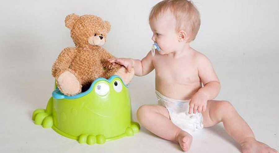 ребенок сажает мишку на горшок