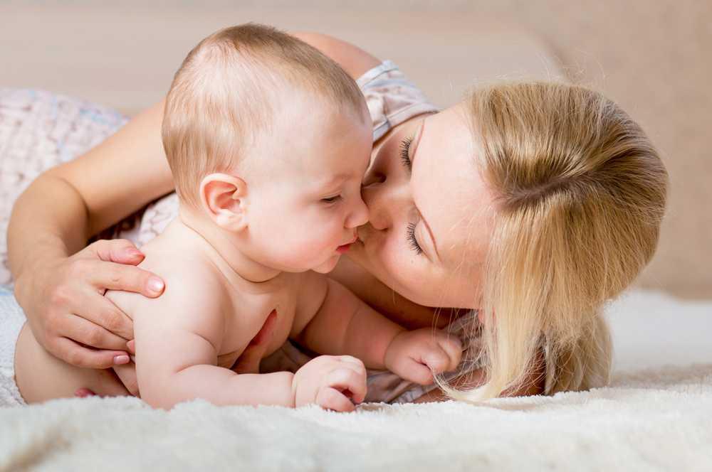 мать целует грудничка