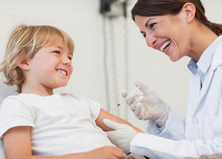 малышу врач делает укол в плечо